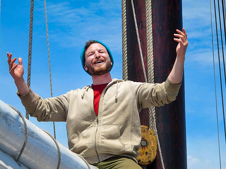 Onboard educator Dustin sings a shanty as we raise the sails