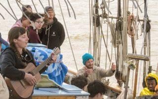Onboard educators sing in honor of Pete Seeger